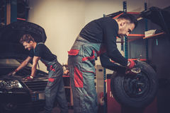 Professional car mechanic balancing car wheel on balancer in auto repair service. Stock Image