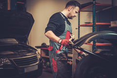 Professional car mechanic balancing car wheel on balancer in auto repair service. Royalty Free Stock Photos