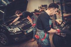 Professional car mechanic balancing car wheel on balancer in auto repair service. royalty free stock photography