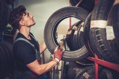 Professional car mechanic choosing new tire in auto repair service. Stock Photos