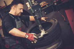 Professional car mechanic replace tire on wheel in auto repair. Professional car  mechanic replace tire on wheel in auto repair service Royalty Free Stock Photo