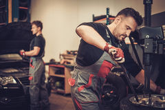Professional car  mechanic replace tire on wheel in auto repair Stock Images