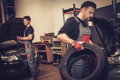 Professional car  mechanic replace tire on wheel in auto repair Royalty Free Stock Image