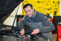 Professional car mechanic smiling to camera while working. Professional car mechanic smiling to the camera while working royalty free stock image