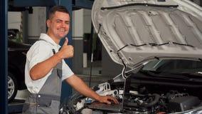Professional car mechanic using laptop while repairing the car royalty free stock photos