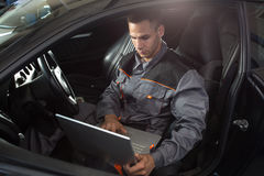 Professional car mechanic working in auto repair service. Diagnostic time stock photo