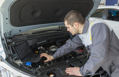 Professional car mechanic working in auto repair service with laptop Royalty Free Stock Photo