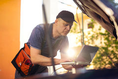 Professional car mechanic working in auto repair service, using Stock Photo