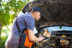 Professional car mechanic working in auto repair service, using Royalty Free Stock Photos