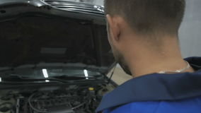 Professional car mechanic working in modern auto repair service and checking engine stock footage