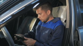 Professional car mechanic working in modern auto repair service and checking engine Stock Image