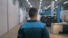 Professional car mechanic working in modern auto repair service and walking around stock video