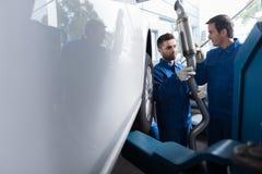Professional car mechanics reparing muffler Stock Photography
