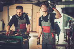 Professional car mechanics working under lifted car in auto repair service. Stock Photos