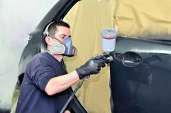 Professional car painter working at a vehicle. Stock Images