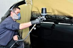 Professional car painter working at a vehicle. Stock Photography