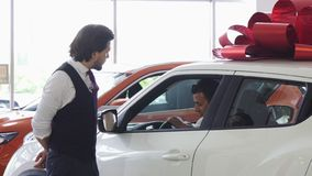 Professional car salesman opening door of a car for his male customer royalty free stock photos