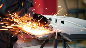 Professional car service - worker grinding metal construction with a circular saw, close up stock video