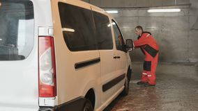 Professional car washman sprays the wax at surface of car. Car washman serves a car in car wash. The worker polishing the car with wax. Man sprays the wax on stock video footage