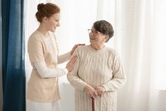 Professional caregiver assisting elderly woman. Professional caregiver in uniform talking to and assisting an elderly women with a cane standing against white royalty free stock images