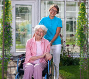 Professional carer behind happy elderly woman Royalty Free Stock Photo