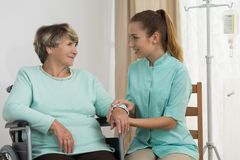 Professional carer nursing elderly lady. Portrait of professional carer nursing elderly disabled lady stock images