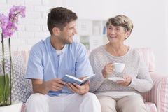 Professional carer reading to senior. Professional carer reading a book to lonely senior women with tea royalty free stock photography