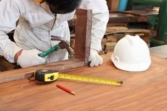 Professional carpenter with safety uniform holding hammer with other tools in carpentry workshop. Stock Images