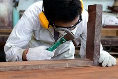 Professional carpenter with safety uniform holding hammer on wood workbench in carpentry workshop. Stock Photography