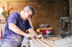 Professional carpenter sanding and refinishing wood surface. royalty free stock photo