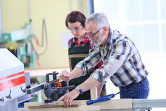 Professional carpenter teaching young woman apprentice Stock Image