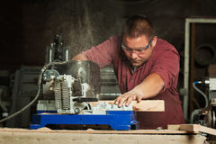 Professional carpenter working with sawing machine. Royalty Free Stock Photo