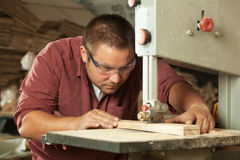 Professional carpenter working with sawing machine. Stock Photography