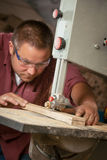 Professional carpenter working with sawing machine. Royalty Free Stock Photography