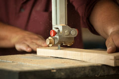 Professional carpenter working with sawing machine in workshop. Stock Photography