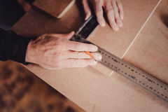 A carpenter uses a square for marking a hole in a furniture part royalty free stock photography