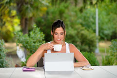 Professional casual woman working online with laptop outside. Professional woman using laptop outside at garden during summer vacation or leisure time. Female Royalty Free Stock Photo