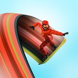 Professional caucasian snowboarder in action. Professional caucasian snowboarder in motion isolated on blue studio background. Fit jumping and flying sportsman stock photography