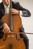 Professional cellist playing his instrument. Professional male cellist playing his cello, classical music solo performance royalty free stock image