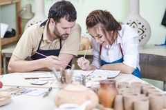 Professional Ceramists Glazing and Painting Ceramic Clay Tiles. Two Professional Ceramists Glazing and Painting Ceramic Clay Tiles in Workshop Together.Group of Royalty Free Stock Images