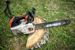 Professional chainsaw on pile of fresh cut wood Royalty Free Stock Photography