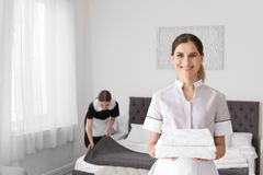 Professional chambermaid holding pile. Of clean towels in bedroom stock photo