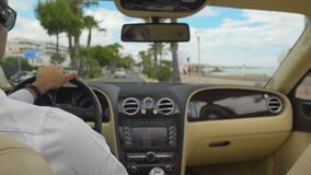 Professional chauffeur driving car in resort city, attentive driver, trip. Stock footage stock footage