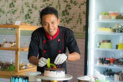 Professional asian pastry chef decorating cake puting red cherry. In top of chocolate cake royalty free stock photos