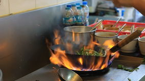 Professional chef in a commercial kitchen cooking flambe stock video