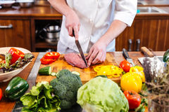 Professional chef cook cutting uncooked meat and fresh vegetables Stock Images