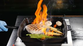 Professional chef cooking flambe style dish on restaurant kitchen. Igniting and stirring frying pan with flaming dish. High cuisine. Slow motion stock footage