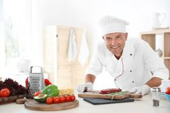 Professional chef cooking meat on table Royalty Free Stock Photos