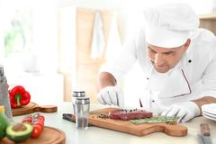 Professional chef cooking meat on table Royalty Free Stock Image