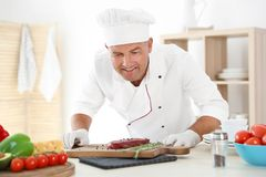 Professional chef cooking meat on table Royalty Free Stock Photo